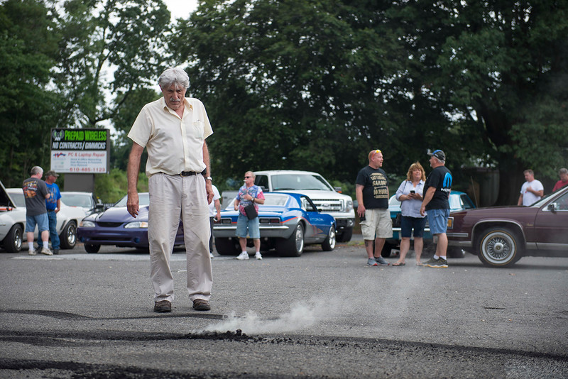 RICK KAUFFMAN - DIGITAL FIRST MEDIA <br /> Pete Eleutheriou, left, checks on a smoldering pile of rubber left after a hot car peeled out of the parking lot of John's Doggie Shop on Saturday.