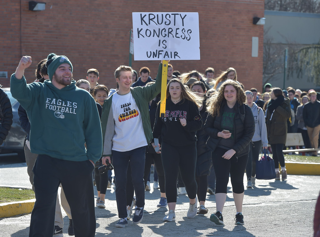 . PETE  BANNAN-DIGITAL FIRST MEDIA      A Haverford High School student holds up a sign as he walks out of school to the Student Unity Rally held at Cornog Field Wednesday morning.  School officials estimated over 900 students took part, including walking  around the track 17 times to remember the students killed in the Florida school shooting. They then held speeches and music before returning to classes. School officials said students organized the event while working with the administration.