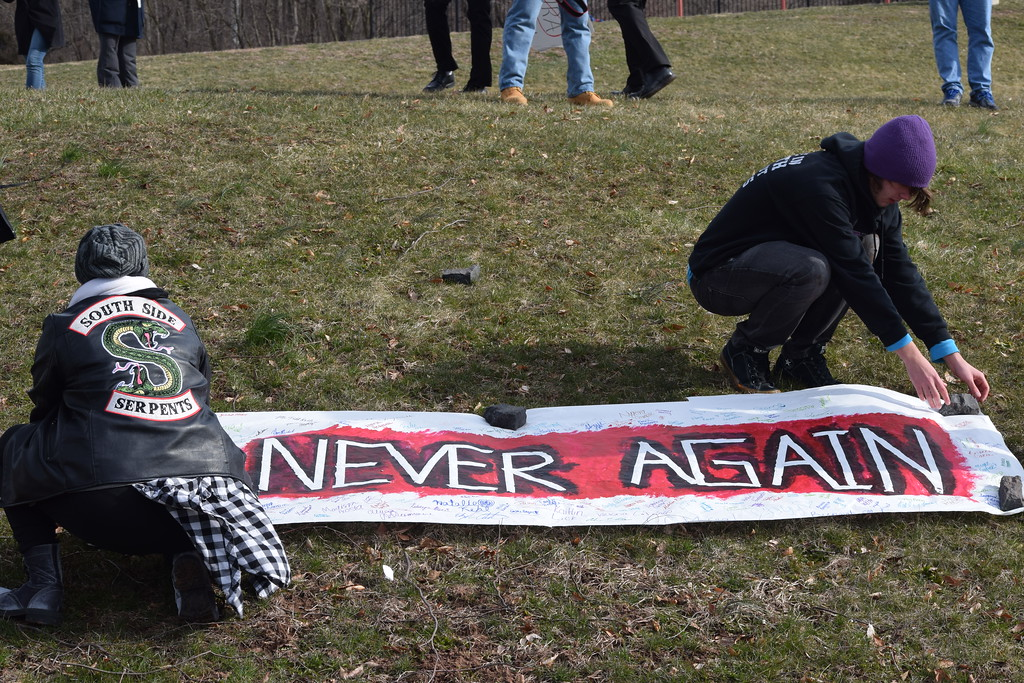 ". Students set up a ""Never Again\"" sign along the grounds of Pottsgrove High School as 700 students walked out and honored the 17 victims of the Marjory Stoneman Douglas shooting.  Photo by Marian Dennis"