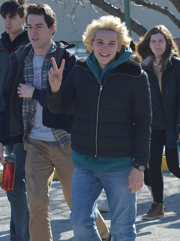 . PETE  BANNAN-DIGITAL FIRST MEDIA      A Haverford High School student holds up the peace sign as he walks out of school to the Student Unity Rally held at Cornog Field Wednesday morning.  School officials estimated over 900 students took part, they walked around the track 17 times to remember the students killed in the Florida school shooting then held speeches and music before returning to classes. School officials said the students organized everything.