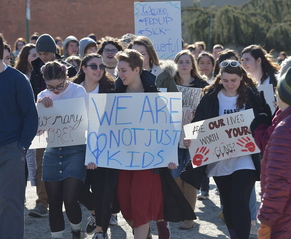 . PETE  BANNAN-DIGITAL FIRST MEDIA      Haverford High School students hold up a signs as they walk  out of school to the Student Unity Rally held at Cornog Field Wednesday morning.  School officials estimated over 900 students took part, including walking  around the track 17 times to remember the students killed in the Florida school shooting. They then held speeches and music before returning to classes. School officials said students organized the event while working with the administration.
