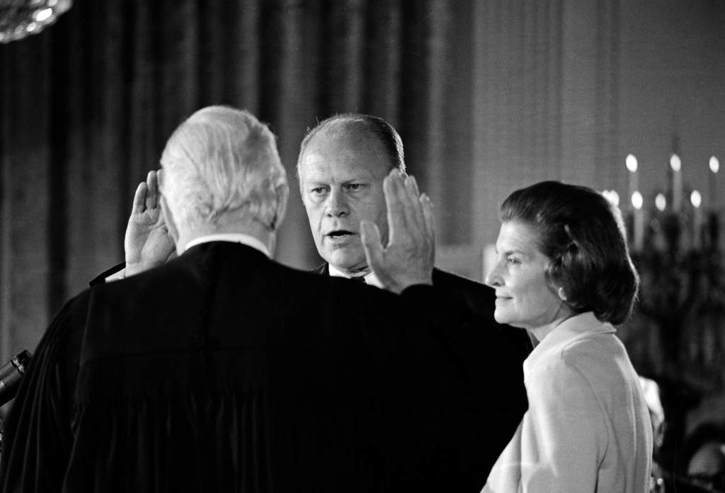 . Gerald R. Ford takes the oath of office as the 38th president of the United States as his wife, Betty, right, stands at his side in the East Room of the White House in Washington, D.C., Aug. 4. 1974.  Administering the oath is Chief Justice of the United States Warren Burger.  Ford is sworn in following the resignation of Richard M. Nixon as chief executive.  (AP Photo)