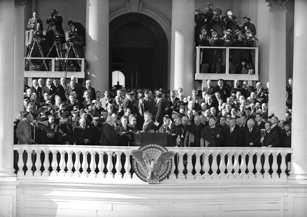 . A general view of the platform at the Capitol in Washington, D.C., Jan. 20, 1941, as President Franklin D. Roosevelt took his oath for his precedent-breaking third term. In group at center Chief Justice Charles E. Hughes, left, administers the oath as C.E. Cropley, clerk of the Supreme Court, holds the ancient Dutch bible. Between the president and Cropley is Thomas Qualters, the president\'s personal aide. At left in first row is the president\'s mother Sara Roosevelt, with first lady Eleanor Roosevelt beside her. At right is the president\'s son, James (in Marine uniform). Next to him is Secretary of State Cordell Hull, an unidentified clergyman, then Majority Leader Alben W. Barkley (D-Kentucky) of the Senate. Vice President-elect Henry A. Wallace is next, then retiring Vice President John N. Garner. (AP Photo)