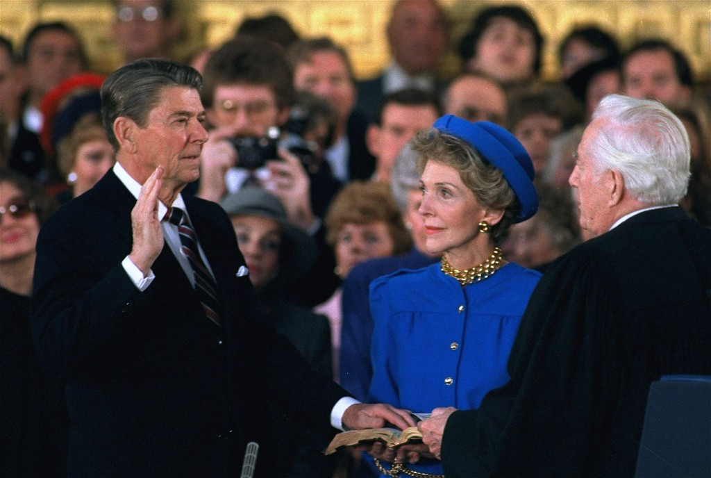 . First Lady Nancy Reagan looks on as President Ronald Reagan is sworn in during ceremonies in the Rotunda beneath the Capitol Dome in Washington Monday, January 21, 1985.  Reagan, forced indoors by a record inaugural freeze, reenacted his oath taking and sounded a second term dedication to his conservative principles. (AP Photo/Ron Edmonds)