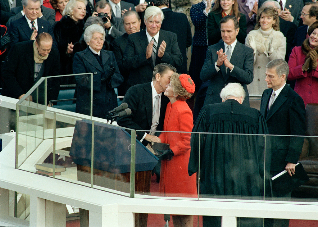 . U.S. President Ronald Reagan kisses his wife, first lady Nancy Reagan, immediately following his swearing-in as the nation\'s 40th president on the west front of the Capitol building in Washington, D.C., Jan. 20, 1981.  Applauding directly behind Reagan are House Speaker Thomas P. O\'Neill, left, and Vice President George Bush, right.  In foreground are Chief Justice Warren Burger, back to camera, and Sen. Mark Hatfield.  (AP Photo)
