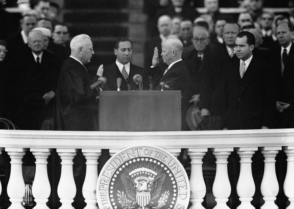 . President Dwight D. Eisenhower takes oath of office for second term in public ceremony at the Capitol in Washington, Jan. 21, 1957 with Chief Justice Earl Warren administering the oath. John T. Fey, center, clerk of the Supreme Court, holds the Bible during the brief swearing in. (AP Photo)