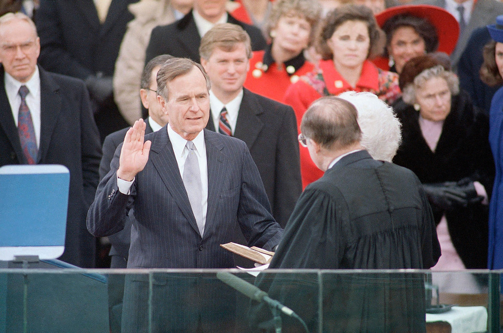 . Pres. George H. W. Bush, left, raises his hand as he takes the oath of office as President of the United States outside the Capitol, Friday, Jan. 20, 1989, Washington, D.C. Vice Pres. Dan Quayle watches from behind. (AP Photo/Ron Edmonds)