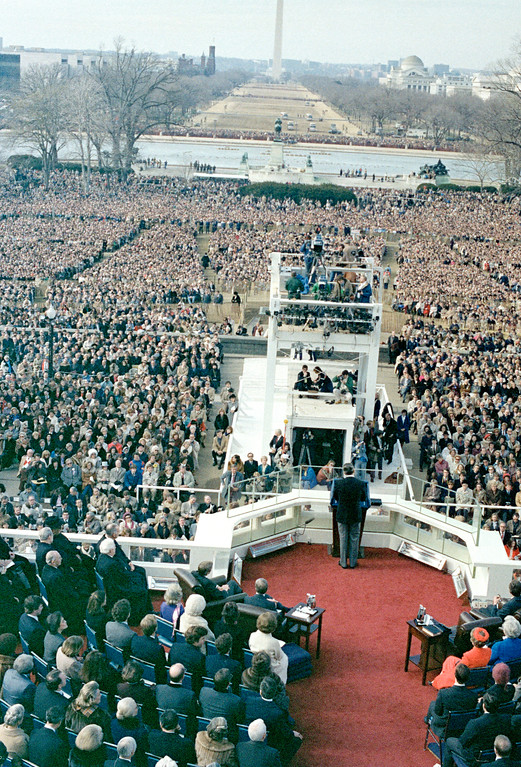. U.S. President Ronald Reagan, lower center with back to camera, speaks following swearing-in ceremony at the Capitol in Washington, D.C., Jan. 20, 1981.  Seated in front row, left side, is Vice President George Bush.  Seated in front row at right is first lady Nancy Reagan, red dress, and Barbara Bush, blue dress.  The Washington Monument is partially visible in the background, center.  (AP Photo)