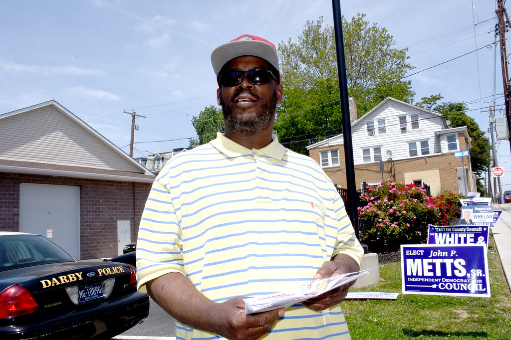 . ANNE NEBORAK-DIGITAL FIRST MEDIA Thomas Davis waits to give out literature to voters outside the Darby Borough\'s Municipal building. He is the son of Janis Davis .
