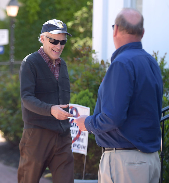 PETE BANNAN _ DIGITAL FIRST MEDIA    Jeff Heim hands Philip Jamison a phamplet for Mark Bruno for judge at Ward 6, at the 1st Presbyterian Church.