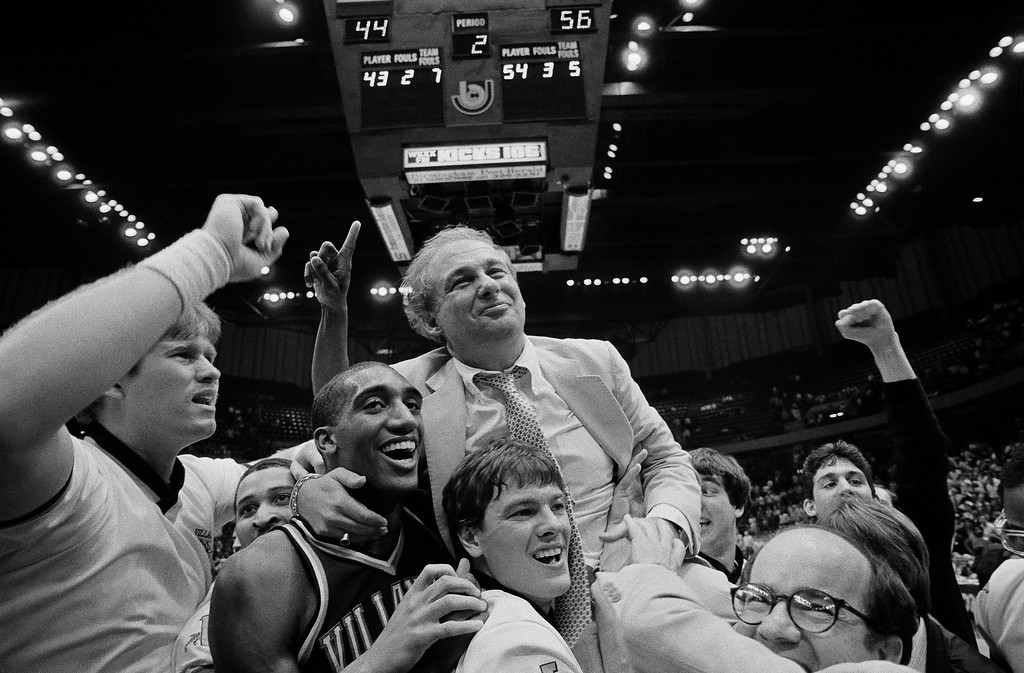 . Villanova coach Rollie Massimino takes a victory ride with his players on the floor after Villanova defeated North Carolina in NCAA Southeast Regional finals, Sunday, March 24, 1985 in Birmingham. Players are Harold Pressley, left, and Brian Harrington. Villanova won 56-44. (AP Photo)