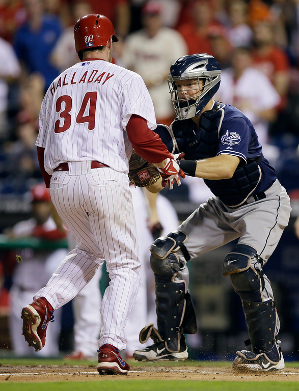 . Philadelphia Phillies\' Roy Halladay, left, is tagged out at home plate by San Diego Padres catcher Nick Hundley after Halladay tried to score on a two-run double by Cesar Hernandez during the first inning of a baseball game, Thursday, Sept. 12, 2013, in Philadelphia. (AP Photo/Matt Slocum)