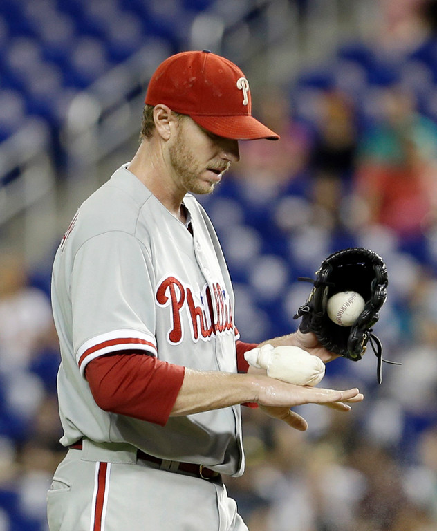 . Philadelphia Phillies\' Roy Halladay (34) bounces the resin bag on his hand in the first inning of a baseball game against the Miami Marlins, Monday, Sept. 23, 2013, in Miami. Halladay left the game with right arm fatigue after walking two of the first three batters he faced. The Marlins won 4-0. (AP Photo/Alan Diaz)
