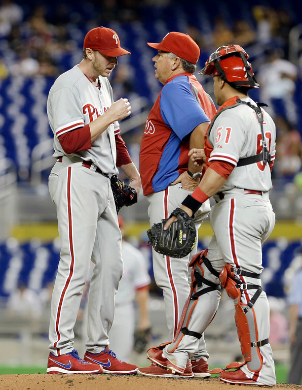 . Philadelphia Phillies pitching coach Rich Dubee, center, talks to Roy Halladay, left, as  catcher Carlos Ruiz (51) arrives at the mound in the first inning of a baseball game against the Miami Marlins, Monday, Sept. 23, 20 13, in Miami.  Halladay left game with an undisclosed injury. Halladay was relieved by Luis Garcia. (AP Photo/Alan Diaz)