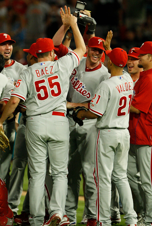 . Philadelphia Phillies starting pitcher Roy Halladay, center, celebrates with teammates Danys Baez (55) and Wilson Valdez (21) after throwing a perfect baseball game against the Florida Marlins, Saturday, May 29, 2010, in Miami. The Phillies defeated the Marlins 1-0. (AP Photo/Wilfredo Lee)