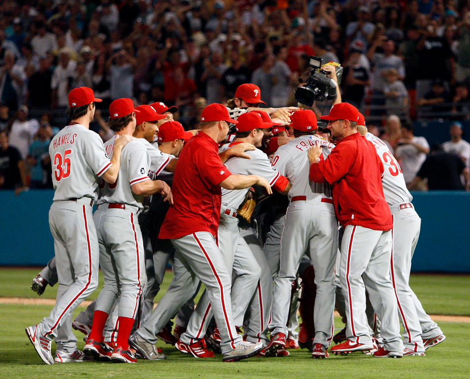 . Philadelphia Phillies starting pitcher Roy Halladay is mobbed by teammates after throwing a perfect baseball game against the Florida Marlins, Saturday, May 29, 2010, in Miami. The Phillies defeated the Marlins 1-0. (AP Photo/Wilfredo Lee)