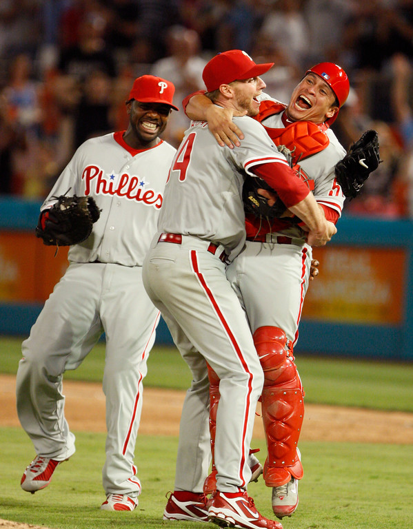 . Philadelphia Phillies starting pitcher Roy Halladay, center, celebrates with Carlos Ruiz, right, and Ryan Howard after Halladay threw a perfect game during a baseball game against the Florida Marlins, Saturday, May 29, 2010 in Miami. The Phillies defeated the Marlins 1-0. (AP Photo/Wilfredo Lee)