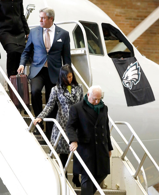 . Philadelphia Eagles head coach Doug Pederson, top, follows team owner Jeffrey Lurie, front, and Lurie\'s wife, Tina Lai, off the plane as the team arrives for the NFL Super Bowl 52 football game Sunday, Jan. 28, 2018, in Minneapolis. The Eagles are scheduled to face the New England Patriots Feb. 4. (AP Photo/Mark Humphrey)