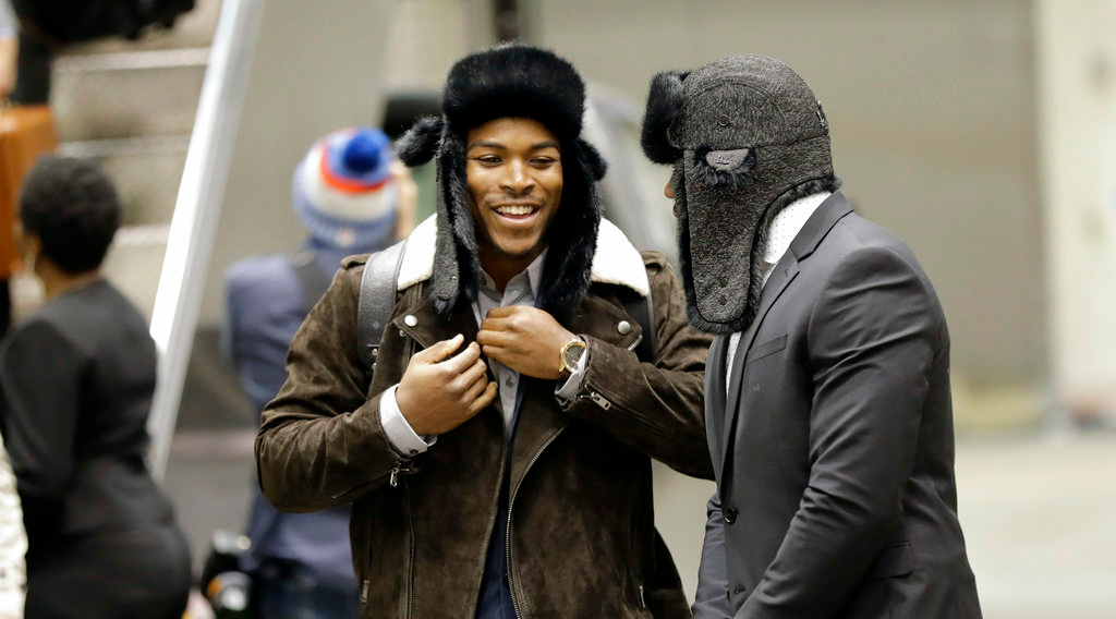 . Philadelphia Eagles running back Corey Clement, left, puts on a winter hat as he arrives with teammates for the NFL Super Bowl 52 football game Sunday, Jan. 28, 2018, in Minneapolis. Philadelphia a a scheduled to face the New England Patriots. (AP Photo/Eric Gay)