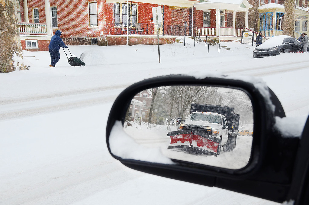 . As reflected in a side-view mirror, a snowplow passes a man snow blowing his sidewalk in the 1000 block of E. High St. in Pottstown during Tuesday\'s snow storm....Photo/Tom Kellly III