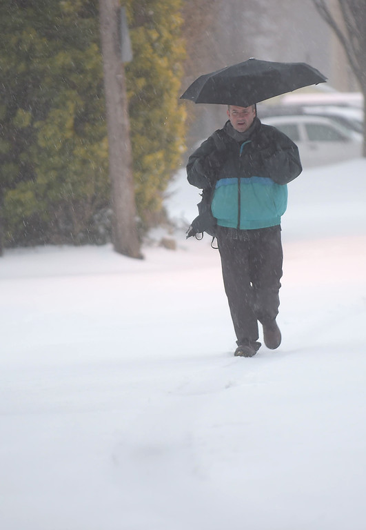 . PETE  BANNAN-DIGITAL FIRST MEDIA      A commuter makes his way to the Ardmore train station Tuessday morning through snow and sleet during the Nor\'easter that closed down much of the region.