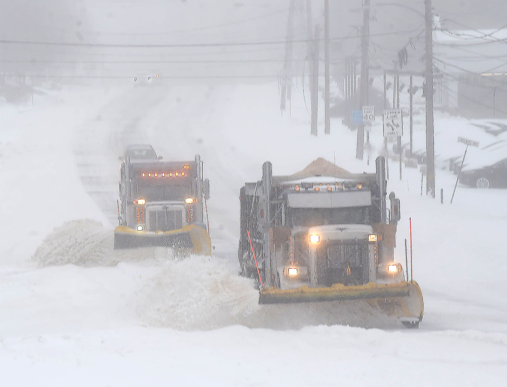 . PETE  BANNAN-DIGITAL FIRST MEDIA     PennDot contracted plow trucks clear snow along Lancaster Ave. in  Devon Tuesday morning. Most people stayed off the road during the morning easing work for plows.