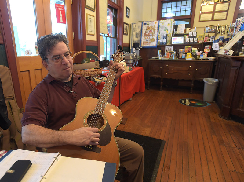 PETE  BANNAN-DIGITAL FIRST MEDIA     On a quiet day at Fabio's and Dannys Station cafe in Wayne, barkeep Mike Lefkowitz had a chance to strum his guitar.