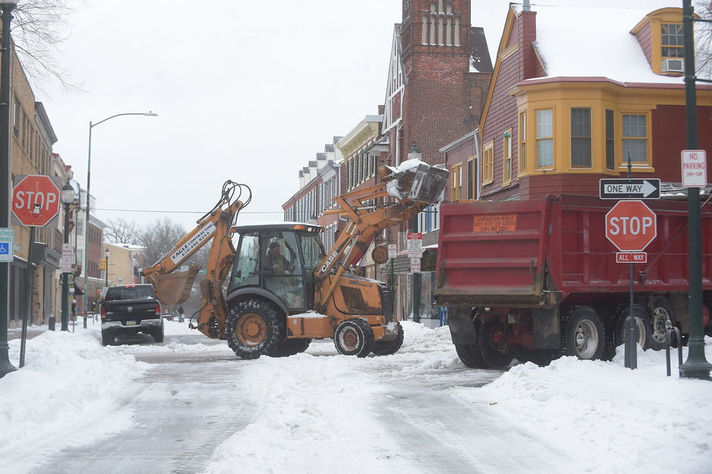 . PETE  BANNAN-DIGITAL FIRST MEDIA      Crews load snow into trucks at Gay and N. New St.  in West Chester  during the tail end of Tuesday\'s. Snow totals were lowered after moisture turned to sleet and rain early in the morning.