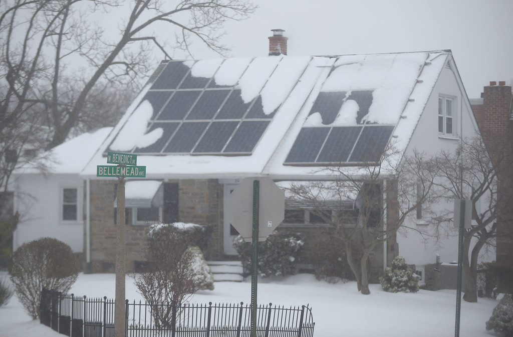 . PETE  BANNAN-DIGITAL FIRST MEDIA    Snow and sleet cover the solar panels on this Havertown houseTuesday morning. The Nor\'easter closed schools and business across the Delaware Valley.