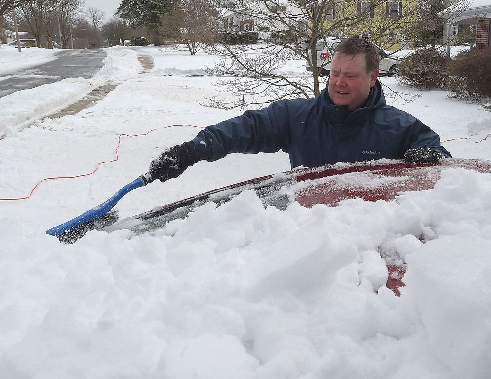 . PETE  BANNAN-DIGITAL FIRST MEDIA      John Marnien sweeps snow off his car in West Chester Tuesday.  Manien said the 5 inches of snow on the ground at 2 a.m. when he went to bed turned to only a few inches after rain and sleet arrived in the early morning.