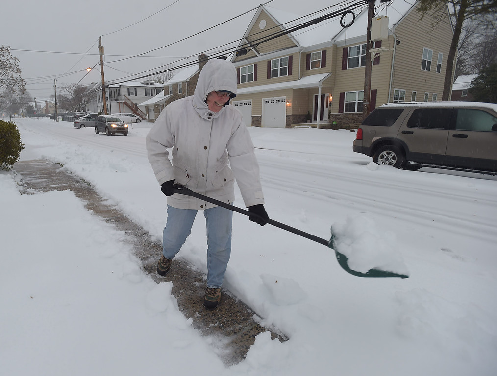 . PETE  BANNAN-DIGITAL FIRST MEDIA     Deb Olszewski clears snow from in front of her Havertown home Tuesday morning March 14, 2017.  Olszewski said she enjoys getting out early to stay ahead of the storm.