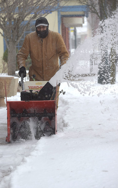PETE  BANNAN-DIGITAL FIRST MEDIA    Georgio Malle clears the sidewalk along Lancaster Ave in Downingtown Tuesday morning.  Snow turned to rain and sleet overnight.