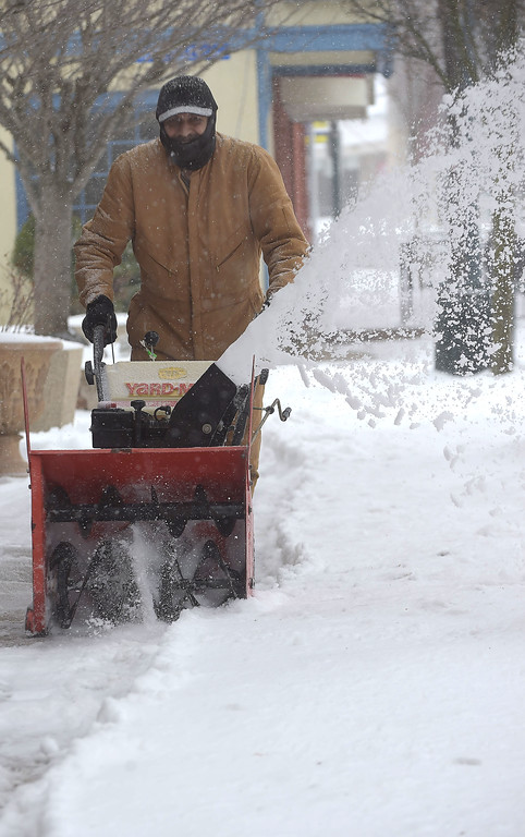 . PETE  BANNAN-DIGITAL FIRST MEDIA    Georgio Malle clears the sidewalk along Lancaster Ave in Downingtown Tuesday morning.  Snow turned to rain and sleet overnight.