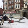 "Ben Moyer clears the gloppy mess in front of his businesses on High Street Tuesday. ""I'm trying to clear some parking spaces. We're open for<br /> business,"" he said. Photo by Evan Brandt"