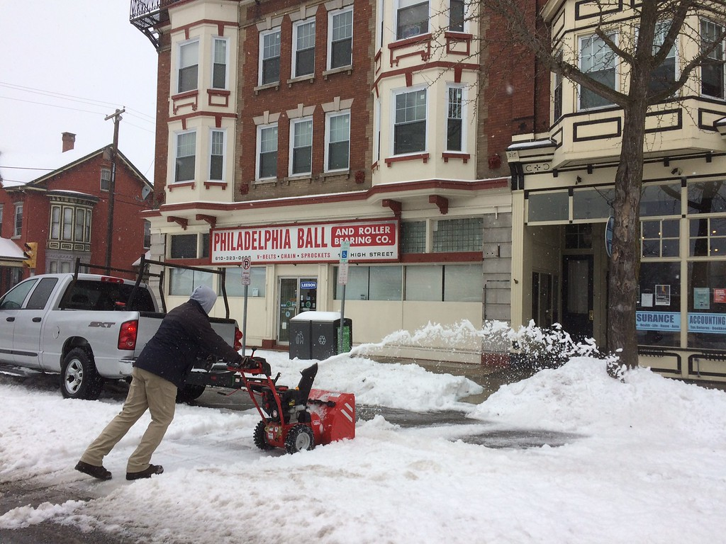 ". Ben Moyer clears the gloppy mess in front of his businesses on High Street Tuesday. ""I\'m trying to clear some parking spaces. We\'re open for business,\"" he said. Photo by Evan Brandt"