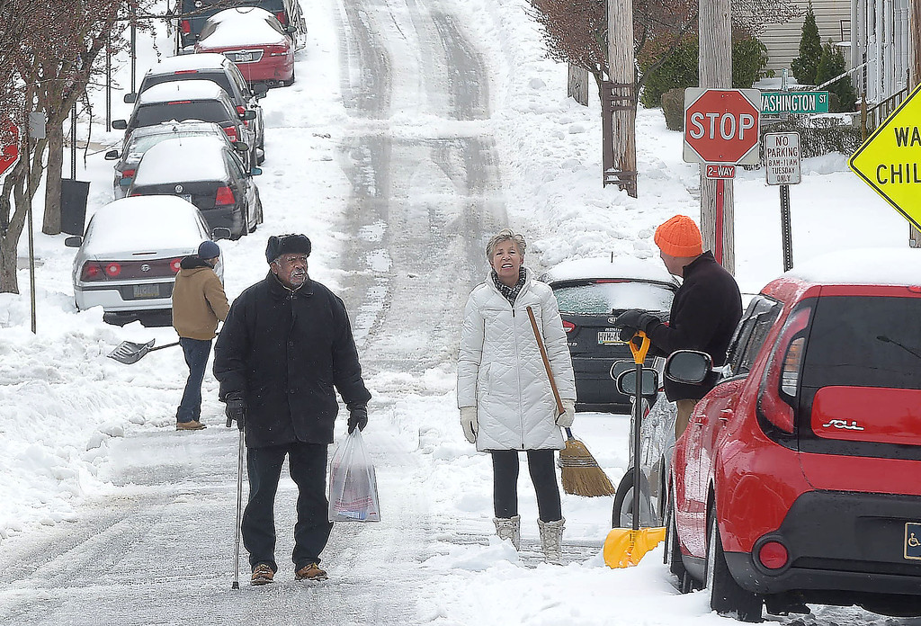 . PETE  BANNAN-DIGITAL FIRST MEDIA     West Chester reisdent, Bob Loper  chats with neighbors Susan Batchelor and Park Messikomer as they shovel their car out on N. New St. in West Chester Tuesday morning. Snow totals were lowered by sleet and rain that fell during the storm.
