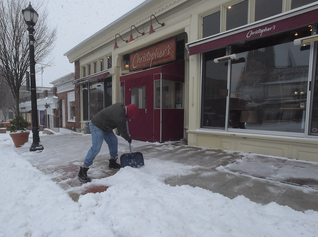 . PETE  BANNAN-DIGITAL FIRST MEDIA    CHristopher Todd clears snow from in front of his restuarant in Wayne Tuesday morning. ,Todd was hoping for a crowd with local school and business closed for the day.
