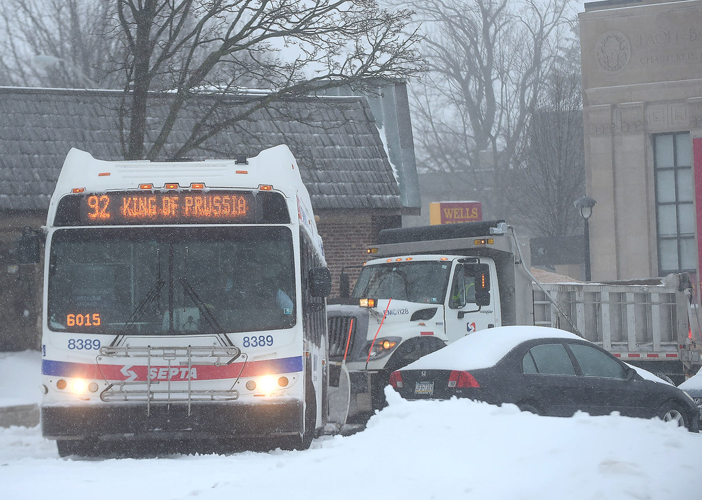 . PETE  BANNAN-DIGITAL FIRST MEDIA     A SEPTA plow truck attempts to clear a path for this bus to back up after it was stuck in snow at the Paoli train station Tuesday morning. Few people ventured out making for light numbers on the regional rail.