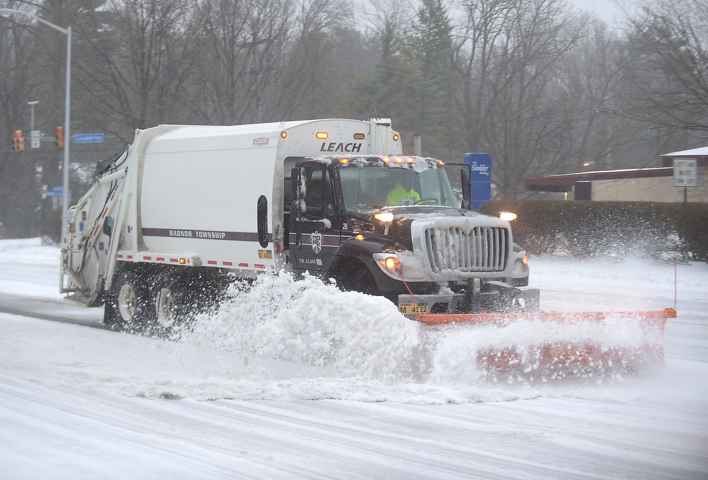 . PETE  BANNAN-DIGITAL FIRST MEDIA     A Radnor Township trash truck clears snow along Lancaster Ave. in  St. David\'s  Tuesday morning. The Township declared a snow emergency to make clearing the roads easier.