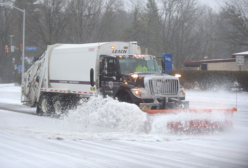 PETE  BANNAN-DIGITAL FIRST MEDIA     A Radnor Township trash truck clears snow along Lancaster Ave. in  St. David's  Tuesday morning. The Township declared a snow emergency to make clearing the roads easier.