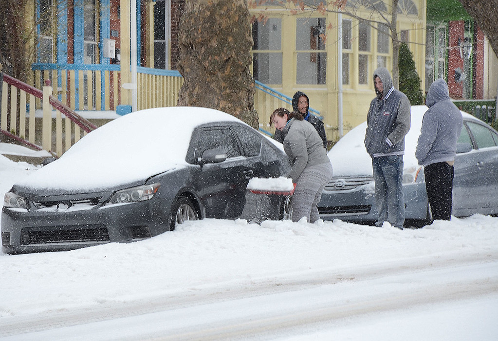 . Three guys watch as Brooke Kissinger shovels out her car on High St. near Price St. in Pottstown during Tuesday\'s snow storm. In defense of the guys...Brooke says she likes to shovel snow and besides the guys were out earlier shoveling and they were taking a break.....Photo/Tom Kelly III