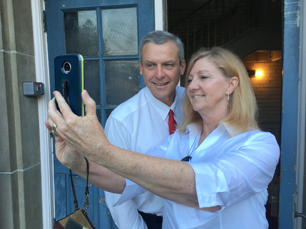 . PETE  BANNAN-DIGITAL FIRST MEDIA        Larry and Heather Arata pose for a selfie in front of the polls at Brookline School in Haverford Tueday morning.