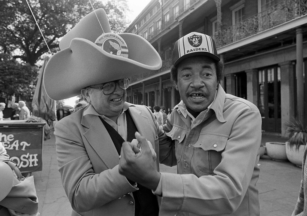 . Philadelphia Eagles fan Bernard J. Giangiulio, left, of Paoli, Penn., and Oakland Raiders fan Robert James of New Orleans trade friendly jabs while touring the French Quarter in New Orleans, Jan. 24, 1981. Crowds in the area have picked up as people arrive for Sunday\'s Super Bowl XV match between the Raiders and Eagles. (AP Photo/Lennox McLendon)