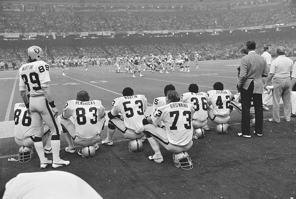. Members of the Oakland Raiders defensive unit watch quarterback Jim Plunkett put the offensive group through its paces against the Philadelphia Eagles during Super Bowl XV in New Orleans, Jan. 26, 1981.  (AP Photo)