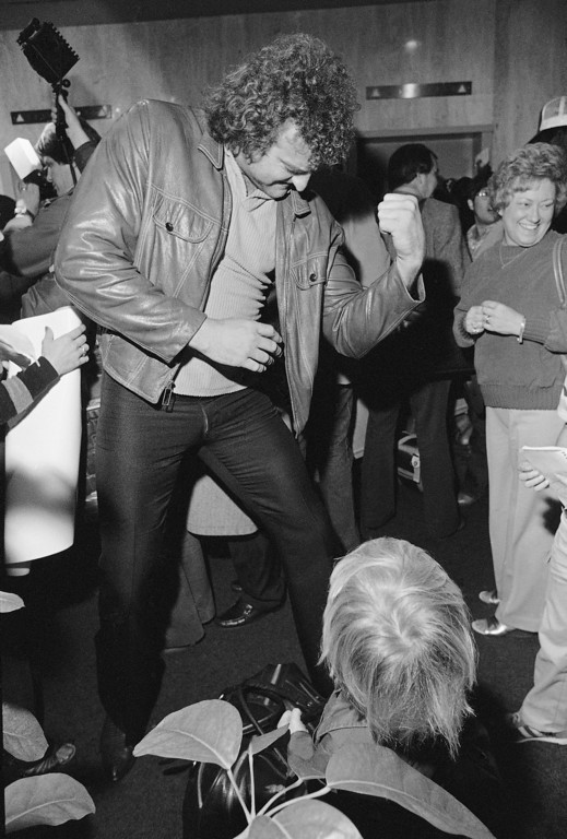. Oakland Raiders 6-foot-8 defensive and John Matuszak flexes his muscle to the delight of a youngster after arriving at a New Orleans motel late Monday afternoon, Jan. 19, 1981. Come Sunday Matuszak will be showing his biceps to the Philadelphia Eagles in Super Bowl XV. (AP Photo/Brian Horton)