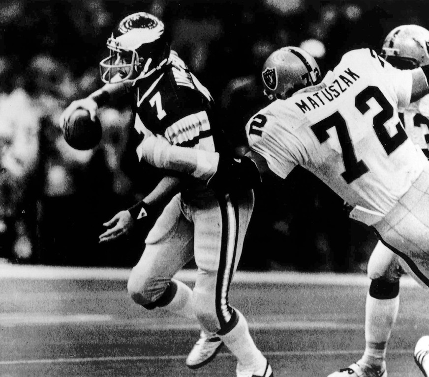 . Philadelphia Eagles quarterback Ron Jaworski scrambles away from Oakland Raiders defensive end John Matuszak in the first half of Super Bowl XV in New Orleans,  Jan. 25, 1981.  (AP Photo)