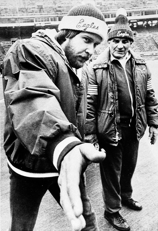 . Eagles quarterback Ron Jaworski reaches forward while conferring with offensive coordinator Sid Gillman, right, during workout at Veterans Stadium in Philadelphia, Jan. 16, 1981. Jaworski is hoping for a hot passing hand on Jan. 25 in the Super Bowl against the Oakland Raiders in New Orleans. (AP Photo/Bill Ingraham)