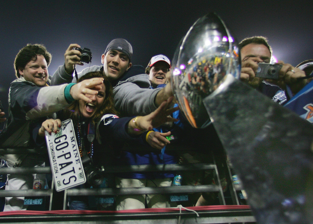 . New England Patriots fans reach to touch the Vince Lombardi Trophy after their team beat the Philadelphia Eagles, 24-21, in Super Bowl XXXIX in Jacksonville, Fla., Sunday, Feb. 6, 2005. (AP Photo/Stephan Savoia)