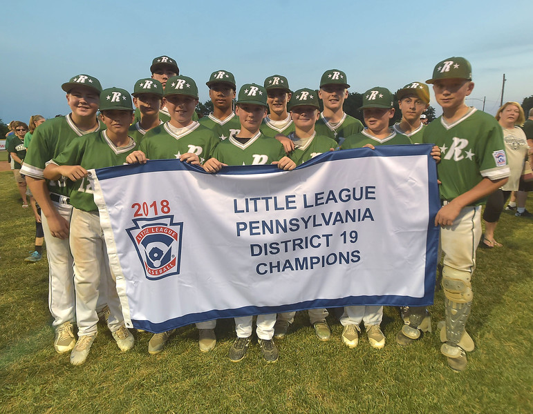 PETE  BANNAN-DIGITAL FIRST MEDIA      Ridley Area players hold the Championship banner after their 13-7 victory over Aston Middletown in the deciding game of the District 19 Little League Majors tournament Tuesday evening.