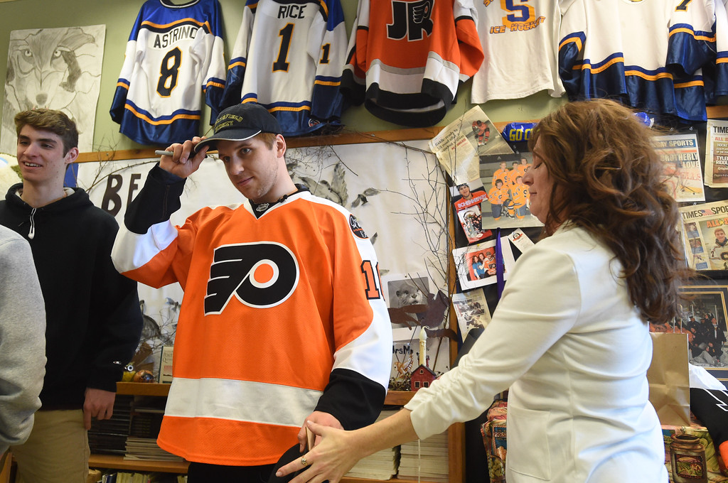 . PETE  BANNAN-DIGITAL FIRST MEDIA      Philadelphia Flyers forward, Braydon Schenn, puts on a Springfield Hockey cap given to her by  teacher Denise Mroz who coined the term �Schennergy�.